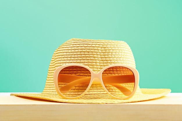 Gafas de sol amarillas y sombrero en un estante de madera