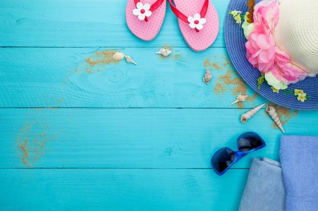 Gafas de sol y arena sobre fondo de madera azul