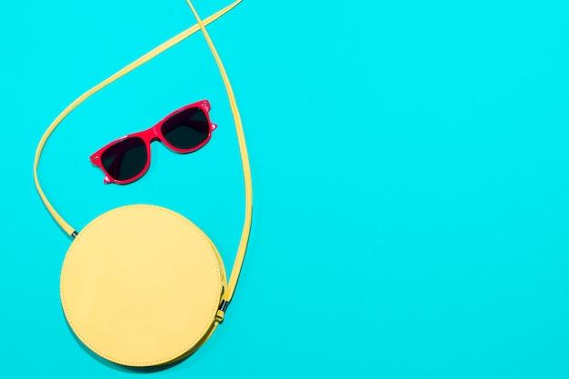 Gafas de sol y bolso sobre fondo azul.