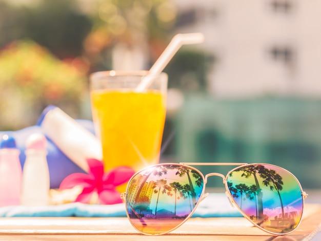 Gafas de sol, champú, loción y jugo de naranja al lado de la piscina