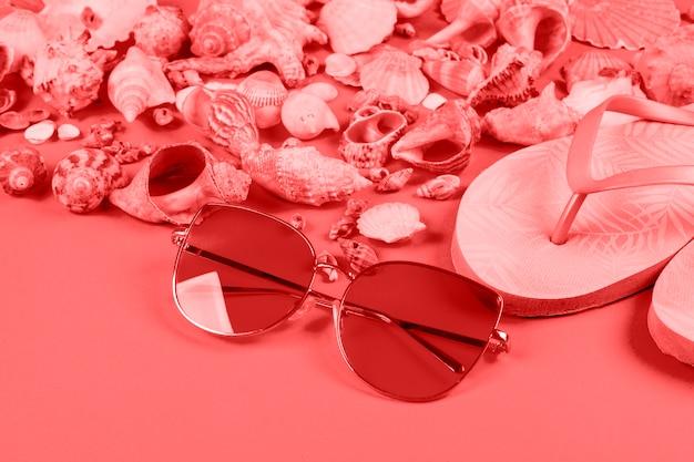 Gafas de sol; conchas y aletas sobre fondo coral
