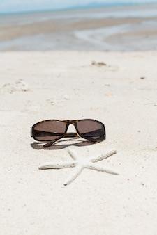 Gafas de sol elegantes y estrellas de mar en la playa de arena blanca