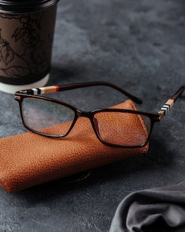 Gafas de sol en el estuche marrón y superficie gris