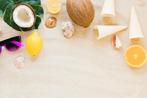 Gafas de sol con frutas exóticas y conchas en la arena.