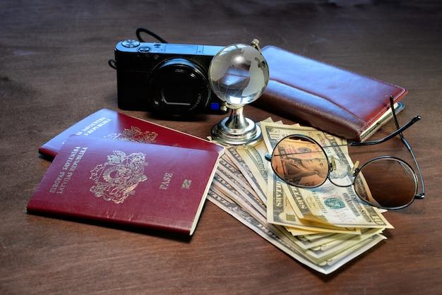 Gafas de sol, un globo de cristal, pasaportes, cámara, cuaderno y dinero en un fondo de madera oscura. concepto de turismo.