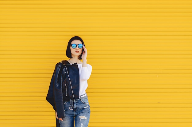 Gafas de sol hermosas de la muchacha en fondo amarillo brillante