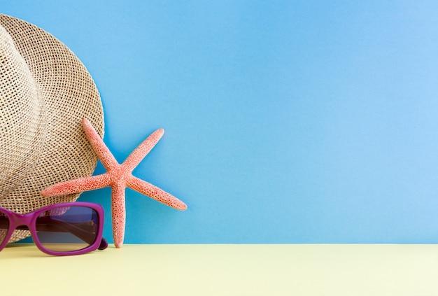 Gafas de sol lilas, sombrero de paja y estrellas de mar sobre la superficie amarilla sobre un fondo azul.