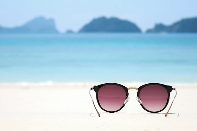 Gafas de sol de moda en la playa del mar bajo el cielo azul claro. vacaciones de verano relajarse fondo con copia spac