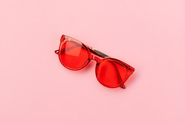 Gafas de sol de moda rojas sobre fondo rosa. concepto de venta de verano de compras de moda