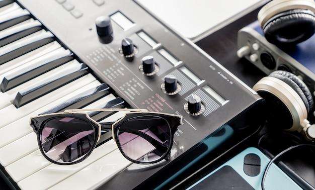 Gafas de sol de moda en el teclado de la música en el estudio
