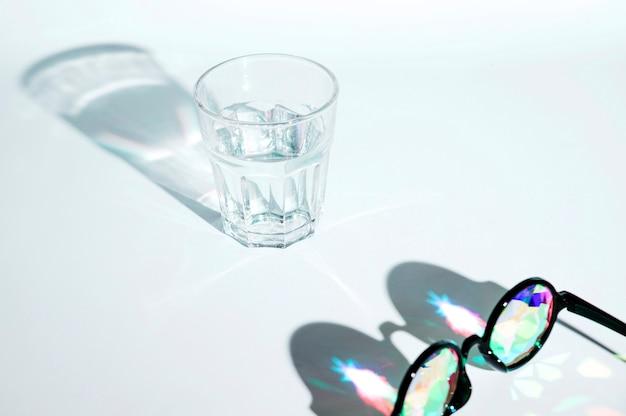 Gafas de sol negras con lente multicolor y vaso de agua con sombra sobre fondo blanco