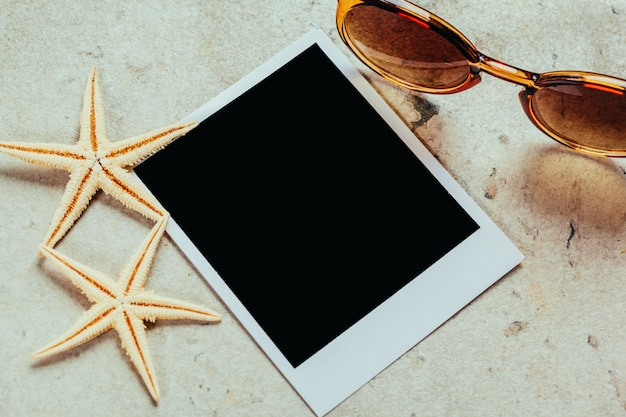 Gafas de sol retro y marcos de fotos polaroid vacías, conchas marinas.