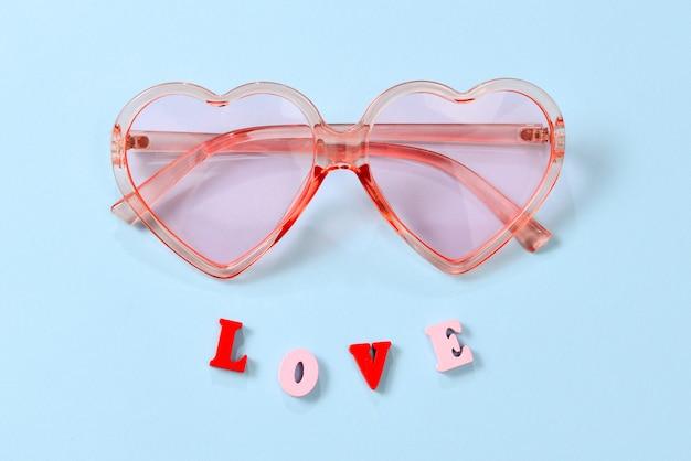 Gafas de sol rosas sobre un fondo azul con texto de amor