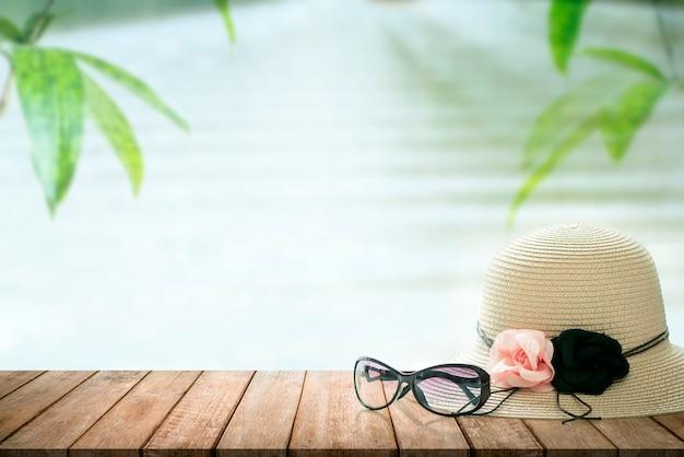Gafas de sol y sombrero de paja en la mesa de madera con fondo de naturaleza