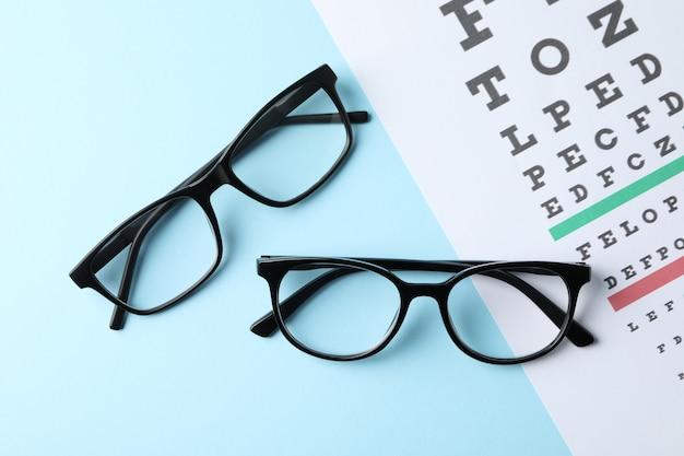 Gafas y tabla de prueba ocular en superficie azul, vista superior