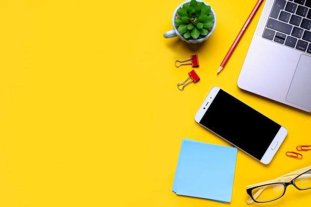 Gafas, teléfono móvil, computadora portátil, flores, pegatinas, clips de papel, papelería sobre un fondo amarillo. lugar de trabajo independiente, empresario, empresario.