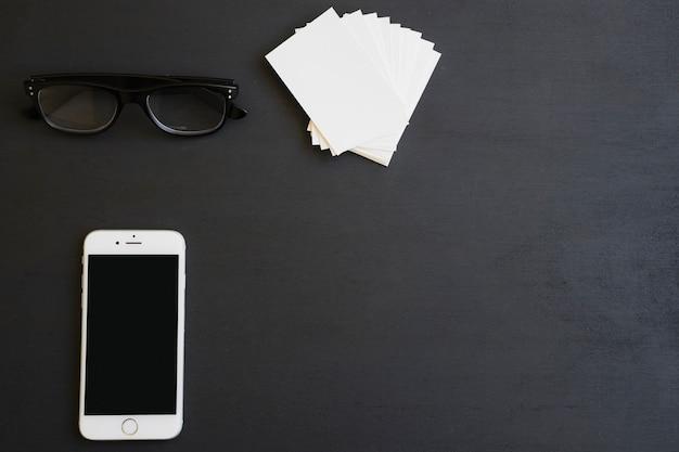 Gafas, teléfono y tarjetas de visita en el escritorio