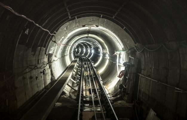 Galería subterránea del túnel del pozo de la mina con vías de ferrocarril en funcionamiento