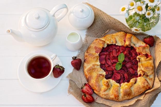 Galette casero recién horneado o pastel de fresa abierto, una taza de té de hierbas, una tetera y un jarrón con un ramo de flores de margarita.