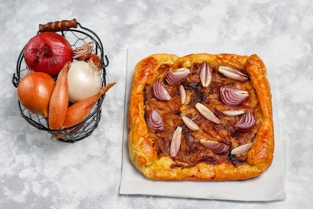 Galette de pastel de cebolla estilo francés con hojaldre y cebolla chalota, cebolla roja, blanca, amarilla, vista superior