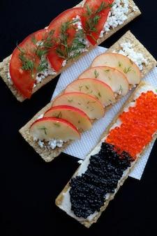 Galleta con caviar, tomate y rodajas de manzana.