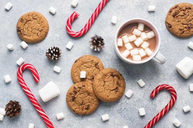 La galleta con chispas de chocolate, el caramelo de caña de navidad taza de cacao y los conos de malvavisco decoraciones en un gris. de cerca