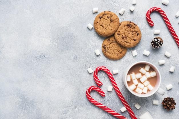 La galleta con chispas de chocolate, el caramelo de caña de navidad taza de cacao y los conos de malvavisco decoraciones en un gris. copyspace marco.