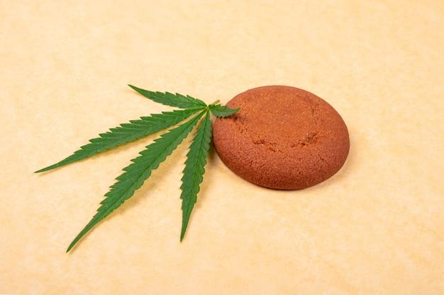 Galleta con chispas de chocolate con hoja verde de primer plano de la planta de cannabis sobre fondo amarillo, dulces con marihuana.