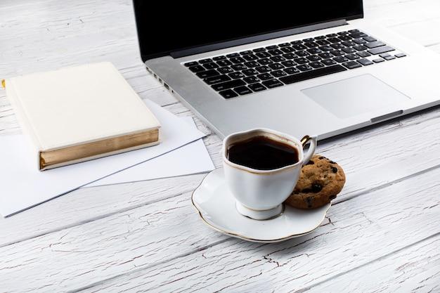 Galleta de chocolate se encuentra en el palte de blanco taza de café antes de una computadora portátil