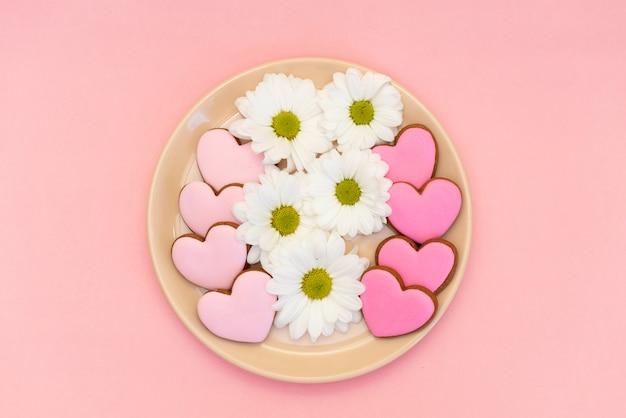 Galleta coginger en forma de corazón sobre fondo rosa pastel
