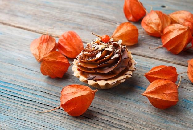 Galleta dulce, pastel con crema y physalis sobre un fondo de madera