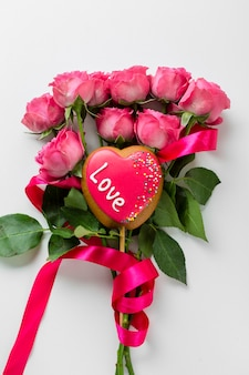 Galleta en forma de corazón en palo con ramo de rosas