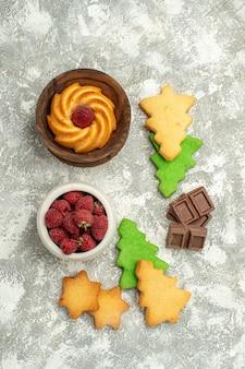 Galleta de galletas de árbol de navidad de vista superior en tazón de fuente con frambuesas en mesa gris