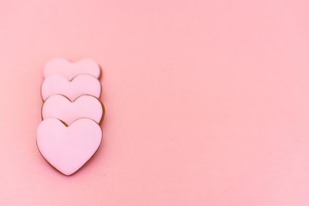Galleta de jengibre en forma de corazón sobre fondo rosa pastel
