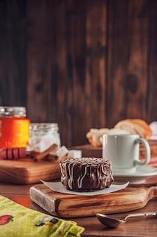 Galleta de miel brasileña cubierta de chocolate sobre la mesa de madera con café y miel de abeja - pao de mel