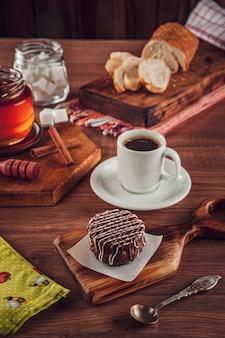 Galleta de miel brasileña cubierta de chocolate sobre la mesa de madera con café y pan de molde - pao de mel
