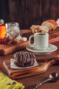 Galleta de miel brasileña cubierta de chocolate sobre la mesa de madera con café - pao de mel