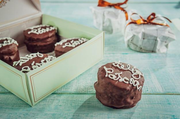 Galleta de miel cubierta de chocolate con una caja de regalo escrita feliz pascua - pao de mel