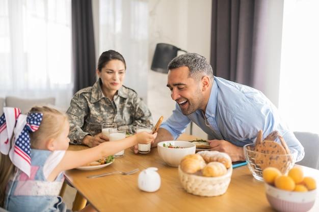 Galleta para papi. encantadora niña generosa dando su galleta a papá mientras desayuna en familia