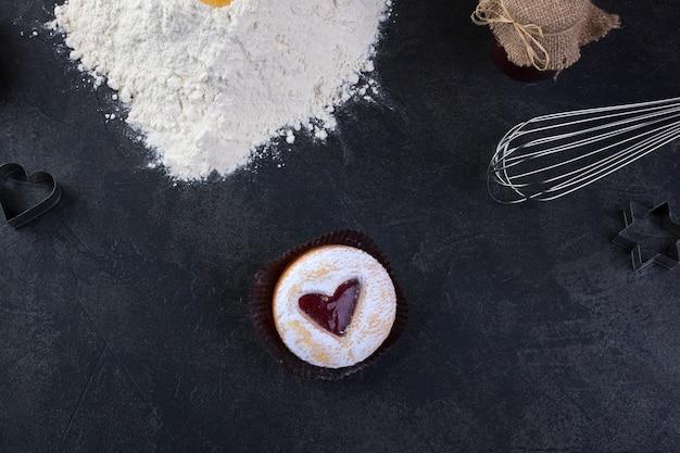 Galleta de pastelería con un corazón de mermelada roja y azúcar glas en polvo