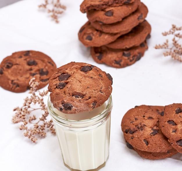 Galleta redonda de chocolate y vaso transparente con leche