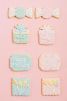 Galletas adornadas del cumpleaños del pan de jengibre dispuestas en fondo rosado