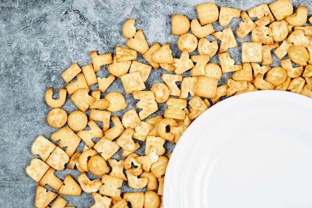 Galletas del alfabeto esparcidas alrededor de un plato vacío.
