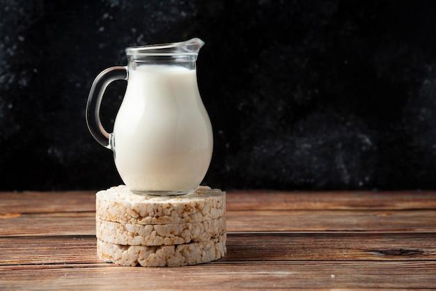 Galletas de arroz y jarra de leche en la mesa de madera.