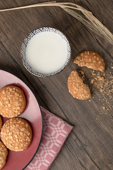 Galletas de avena agrietada con semillas y tazón de leche fresca en la mesa de madera