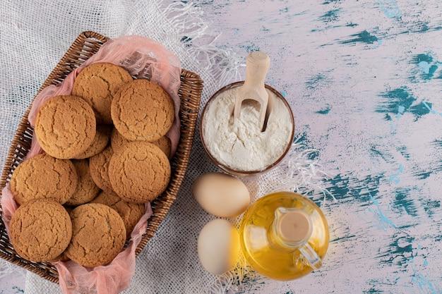 Galletas de avena en una bandeja de cesta de madera con ingredientes alrededor.