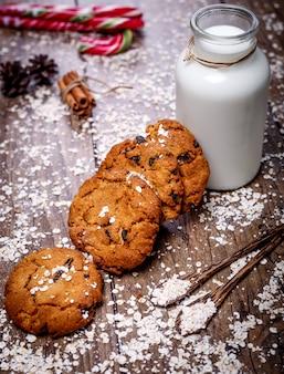 Galletas de avena caseras con nueces, pasas, bastón de caramelo y una botella de leche sobre fondo de madera oscura.