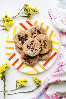 Galletas de avena con chocolate en un plato con tela brillante y flores.