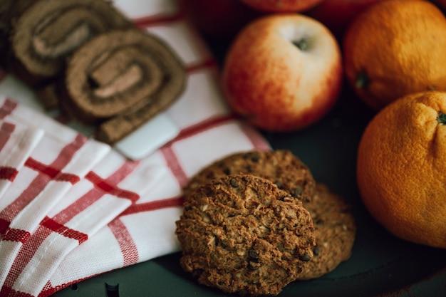 Galletas de avena con manzanas y mandarinas en la toalla roja marcada.