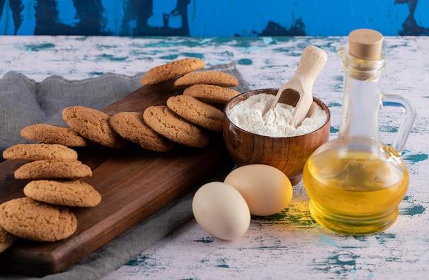 Galletas de avena en un plato de madera con ingredientes alrededor.